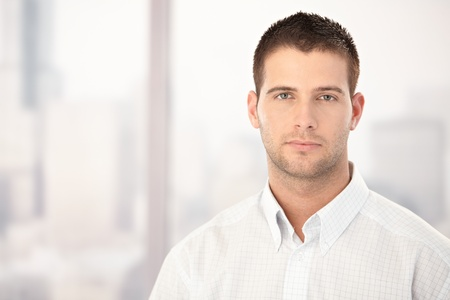 severity: Portrait of handsome young man front of window.