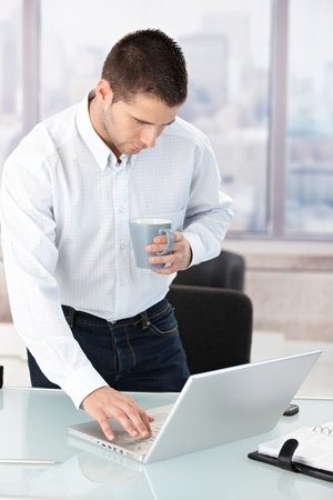 Young man working on laptop in bright office, drinking tea. photo
