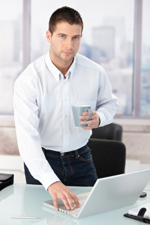 severity: Young male casual office worker using laptop in bright office. Stock Photo