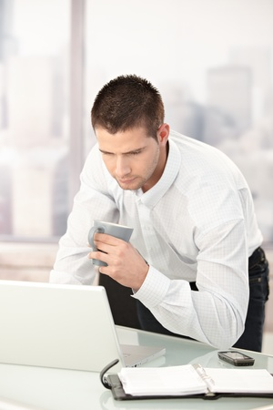 Young businessman busy by working in bright office. photo