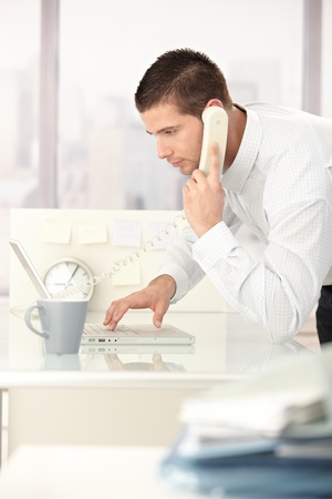 Young man working on laptop in bright office, using phone. photo