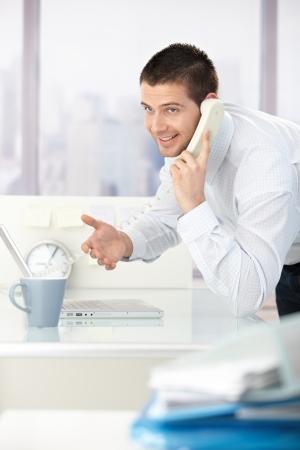 Joven empresario hablando por teléfono, sonriendo en Oficina brillante. Foto de archivo - 8747248