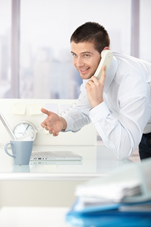 Young businessman talking on phone, smiling in bright office. photo