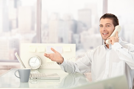 Handsome young businessman chatting on phone in bright office. photo