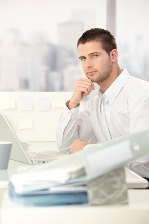 Young male casual office worker sitting at desk in office. photo