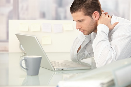 weary: Young man working on laptop, looking tired, sitting at desk. Stock Photo