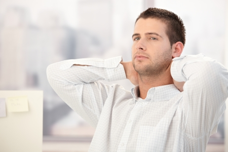 weary: Young man thinking with hands on back of the neck. Stock Photo