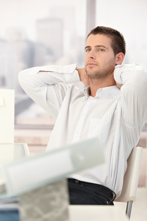 severity: Tired businessman relaxing in chair with hands on back of the neck. Stock Photo