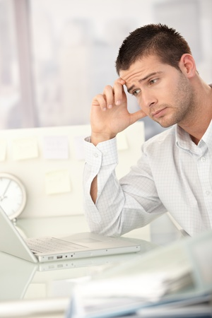 Tired businessman working on laptop in bright office. photo