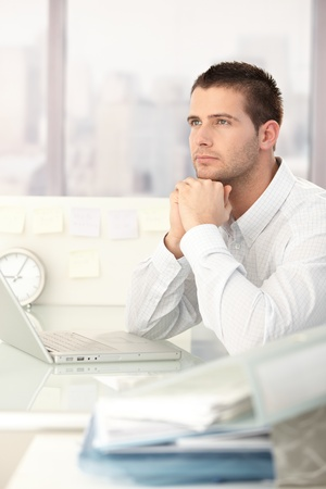 Daydreaming businessman sitting at desk in bright office. photo