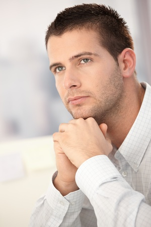 severity: Portrait of goodlooking young man sitting at desk.
