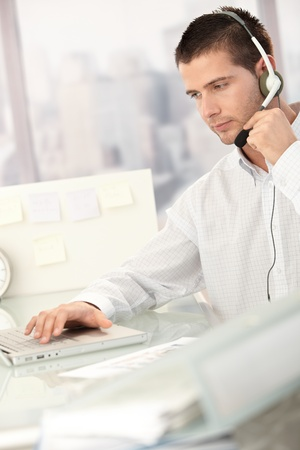Young male dispatcher working in bright office. Stock Photo - 8747260