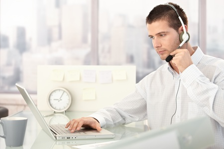Male customer service operator working in bright office. photo