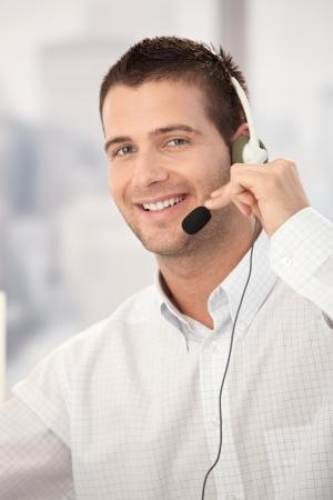 poner atencion: Retrato de operador de servicio al cliente feliz trabajando en la Oficina brillante.