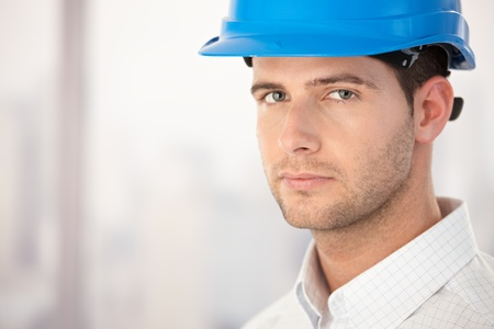 Portrait of handsome young architect wearing helmet. photo