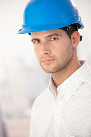 Portrait of goodlooking young architect wearing helmet. photo