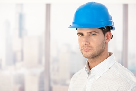 Portrait of handsome young engineer wearing hardhat. photo
