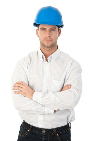 unsmiling: Goodlooking young architect standing arms crossed, wearing hardhat.
