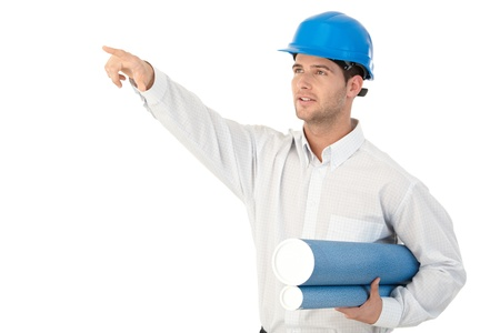 architectural architect: Young architect on site inspection, wearing hardhat, pointing to distance. Stock Photo