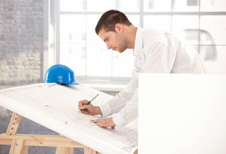 planos arquitecto: Joven ingeniero ocupado por trabajo, utilizando la tabla de dibujo. Foto de archivo