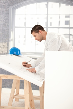 Handsome young architect drawing plans in office. photo
