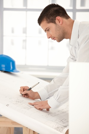 Young goodlooking engineer making plans on drawing table. photo