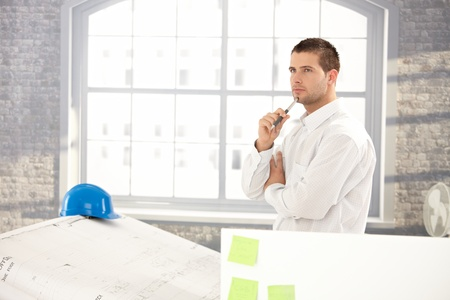Goodlooking young architect making plans on paper. photo