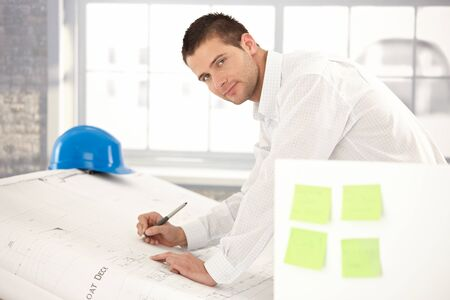 Handsome young engineer drawing plans in bright office. photo