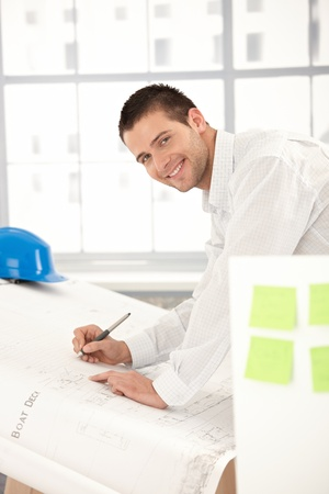 architect office: Happy young architect working in bright office. Stock Photo