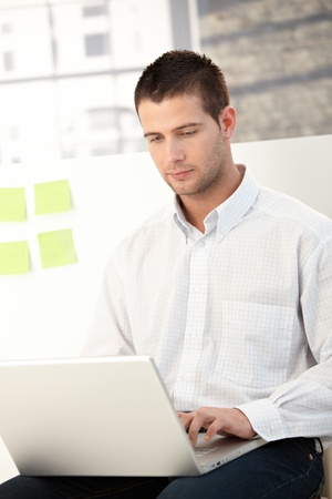 Casual office worker using laptop in bright office.