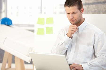 stubbly: Young architect working on laptop in bright office. Stock Photo