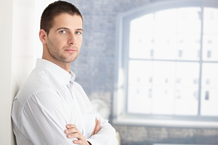 Handsome young man standing arms crossed by wall. photo