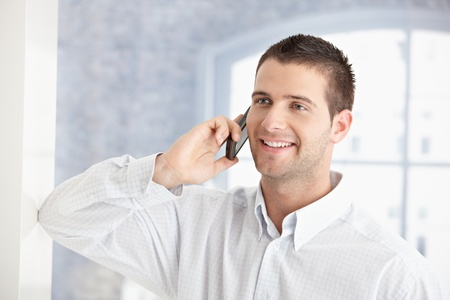 stubbly: Handsome young man talking on mobile phone, smiling.