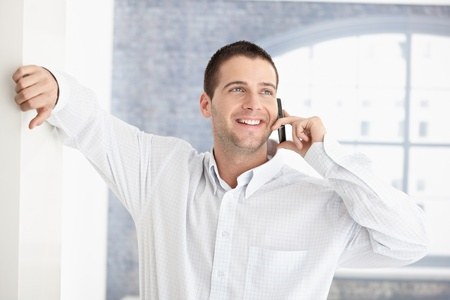 cellular phones: Casual young man chatting on mobile, smiling.