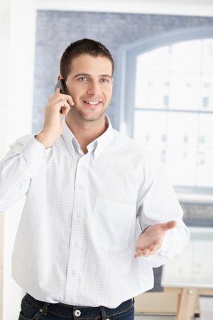 talk to the hand: Happy young man talking on mobile phone. Stock Photo