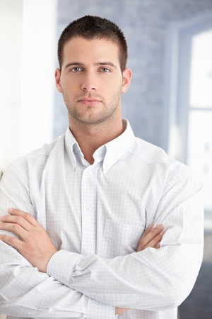 stubbly: Handsome young businessman standing arms crossed.