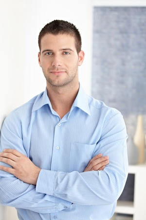 stubbly: Casual young man standing arms crossed, smiling. Stock Photo