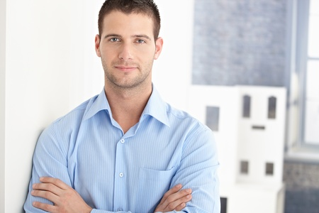 stubbly: Handsome young man smiling arms crossed. Stock Photo