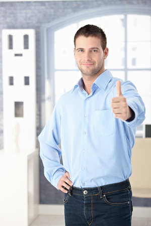 stubbly: Confident young man smiling and showing thumb up.