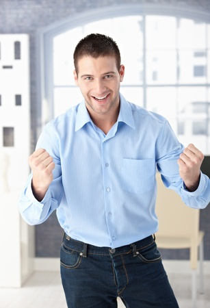 clenched: Happy young man celebrating success with clenched fists, smiling.