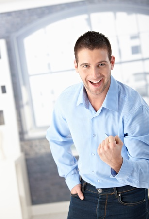fist clenched: Successful young man celebrating with clenched fist, smiling happily.