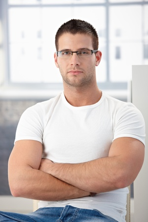 offish: Handsome, sporty man sitting, wearing glasses.
