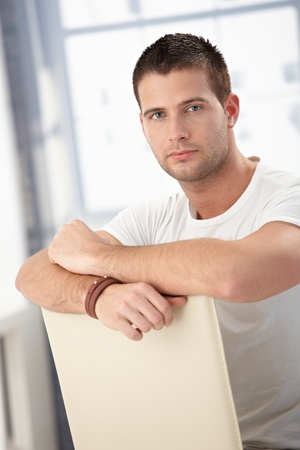 Handsome young man sitting conversely on chair. Stock Photo - 8747259