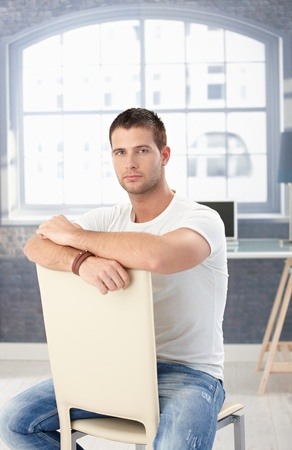 offish: Goodlooking young man in Tshirt and jeans sitting conversely on chair.