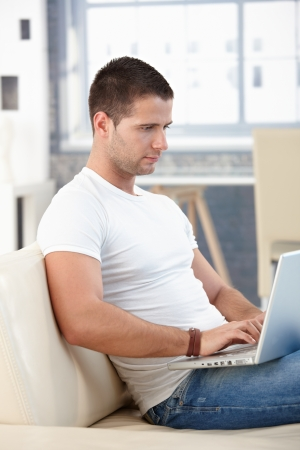 Athletic young man sitting on sofa, browsing internet on laptop. photo