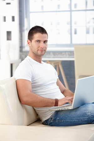 Sporty young man browsing internet at home, sitting on sofa. photo