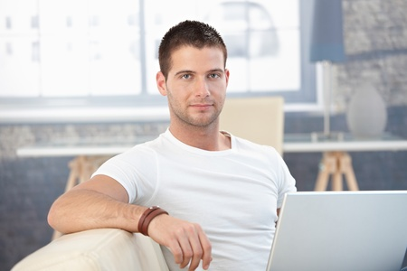 Portrati of handsome young man using laptop at home. photo
