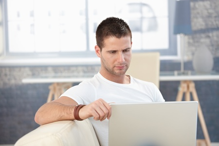 Goodlooking young man working on laptop at home. Stock Photo - 8747227