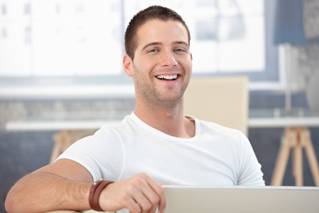 bristly: Handsome young man laughing happily at home.