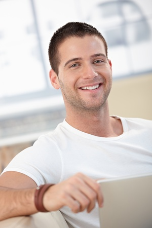 young unshaven: Portrait of happy young man using laptop at home.